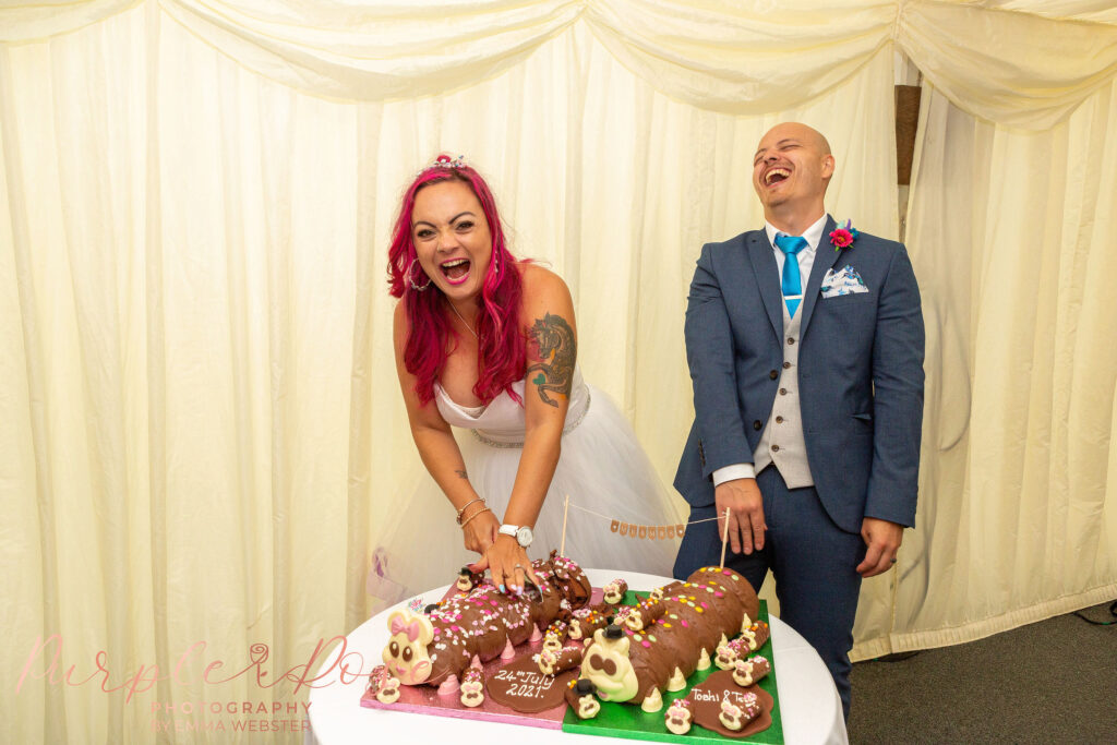 Bride and groom with their caterpillar wedding cake