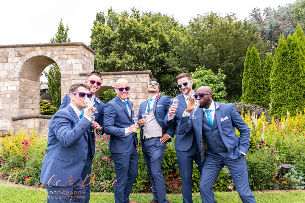 Groomsment wearing sun glasses and enjoying a drink