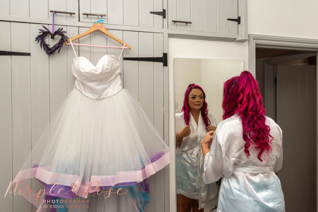 Bride looking in mirror stood next to her wedding dress